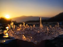 Icicles a piece of ice in hand against the backdrop of a mountain river at sunset stock images