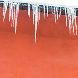 Icicles. On the red house, abstrakt background Royalty Free Stock Photos