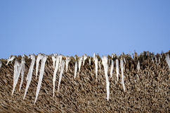 Icicles retro straw roof background blue sky Royalty Free Stock Photo