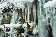 Icicles on rock face Royalty Free Stock Photo