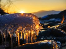 Icicles on the rocks on a mountain river at sunset royalty free stock photo