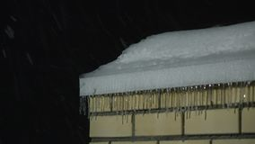 Icicles on the roof of brick building and snowfall at night 4K shot stock video footage