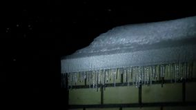 Icicles on the roof of brick building and snowfall at night super slow motion shot stock footage