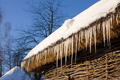 Icicles on a roof of cottage across blue sky Stock Images