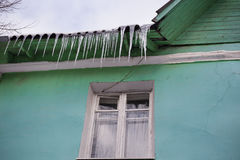 Icicles on roof. Icicles on green roof of old house Stock Images