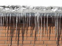 Icicles on the roof of the house royalty free stock images