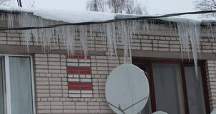 Icicles on the roof of the house. panning left to right.  stock footage