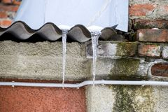 Icicles on the roof. Insecure roof. Freezing water in the icicle. Icicles on the roof. Insecure roof. Freezing water in the icicle Royalty Free Stock Photos