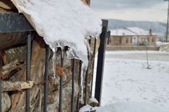 Icicles on a roof. Large icicles on the roof of a small stock house in snowy yard Stock Image