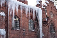 Icicles in winter on the roof of a red brick house stock photo