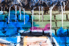 Icicles on roof of shed with painted brick wal Stock Photography