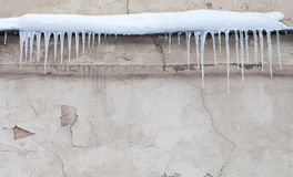 Icicles on the roof. Vintage shabby wall background. Cold winter weather concept. Soft focus Royalty Free Stock Image