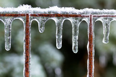 Icicles on a rusted fence after an ice storm. Stock Photo