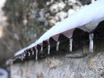 Icicles on rusty iron roof royalty free stock image