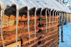 Icicles on slate roof of a log cabin Stock Images