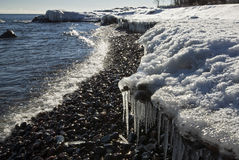 Icicles and snow cover the shore of Lake Superior Stock Photos