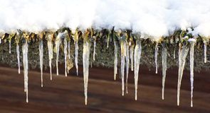 Icicles and snow - housetop Royalty Free Stock Image