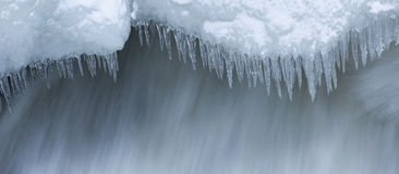 Icicles and snow near flowing water Royalty Free Stock Photo