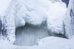 Icicles and snow near flowing water Stock Image