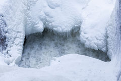 Icicles and snow near flowing water Royalty Free Stock Images