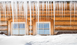 Icicles and snow on an old wooden cottage Stock Photo