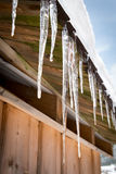 Icicles and snow on an old wooden cottage Royalty Free Stock Photos
