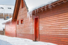 Icicles and snow on an old wooden cottage Royalty Free Stock Images