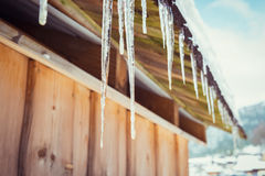 Icicles and snow on an old wooden cottage Royalty Free Stock Photo