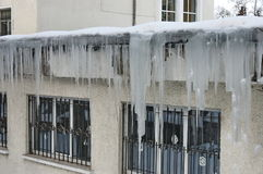 Icicles from a snow rooftop during  winter Stock Photography