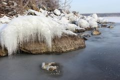 Icicles on a stone on a freezing river. Icicles  on a stone on a freezing river  , Ob reservoir, Siberia, Russia Royalty Free Stock Images