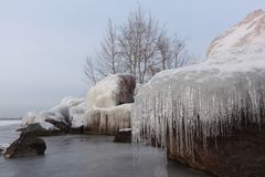 Icicles on the stones on the freezing river in autumn. Ob Reservoir, Siberia, Russia Royalty Free Stock Photography