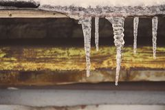 Icicles on vintage roof closeup. Winter weather concept. Froze and ice background. Snow and icicle. Melting icicles. Icicles on vintage roof closeup. Winter royalty free stock photos