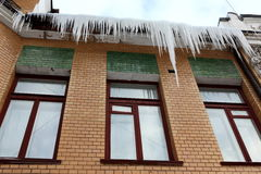 Icicles which are hanging down from a roof. Stock Photography