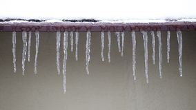 Icicles which are hanging down from a roof stock video