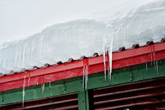 Icicles on a wooden chalet roof Royalty Free Stock Photo