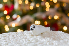 Icing on Christmas cake with tree lights Stock Images