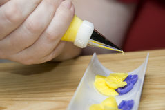 Icing Flowers. A baker uses royal icing to create pansy flowers in a white tray Stock Images