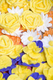 Icing Flowers Background. A background of royal icing flowers including daisies, roses, and pansies Stock Photo