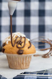 Icing frosting being put onto home made chocolate chip muffins. Home made chocolate chip muffins with icing frosting being applied Royalty Free Stock Images