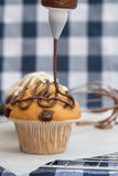 Icing frosting being put onto home made chocolate chip muffins Royalty Free Stock Photo