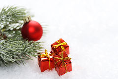 Icing pine branch with red matt christmas ball and three christmas red gift box with yellow bow on snow Stock Photos
