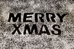 Icing sugar on a black stone, text Merry xmas Royalty Free Stock Photo