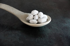 Icing Sugar coated Almonds on big Spoon Royalty Free Stock Images