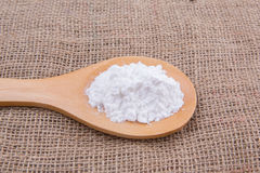 Icing Sugar I. White refine sugar in wooden spoon on gunny sack background Stock Photos