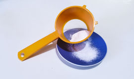 Icing sugar. In orange sieve and blue plate Royalty Free Stock Image