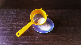 Icing sugar. In orange sieve and blue plate Royalty Free Stock Photos