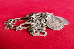 ICJ metal necklace and medal. Metal medal of the International Court of Justice hooked with a metal necklace against a red fabric background Stock Images