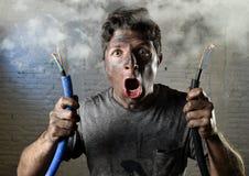 Icke-utbildad man som sammanfogar elektrisk kabel som lider elektrisk olycka med den smutsiga brända framsidan i roligt chockuttr Arkivfoto