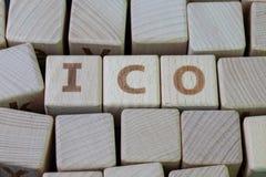 ICO,提供为隐藏货币产业概念,与字母表的立方体木块的最初的硬币结合在黑色的词ICO 库存照片