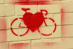 Icon on the benefits of bicycle. On the bright red paint wall painted bike and heart Stock Photos